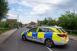 """© Licensed to London News Pictures. 02/06/2021. Aylesbury, UK. A police vehicle blocks traffic following a fatal incident, believed to involve an electrical worker, in Fairford Leys Way, Aylesbury. South Central Ambulance Service (SCAS) were called at 11:30am and sent a rapid response vehicle, ambulance crew, ambulance o fficer and the Thames Valley Air Ambulance to assist one patient. A Thames Valley Police spokesperson said: """"This was the sudden death of a man in Fairford Leys Road, Aylesbury, which was reported at around 11.40am today (2/6). Officers attended along with paramedics. Next of kin have been made aware and are being supported. The death is not being treated as suspicious."""" Photo credit: Peter Manning/LNP"""