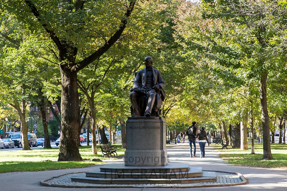 Couple strolling in Commonwealth Avenue Mall near William Lloyd Garrison statue sculpted by Olin Levi Warner, in Boston, USA