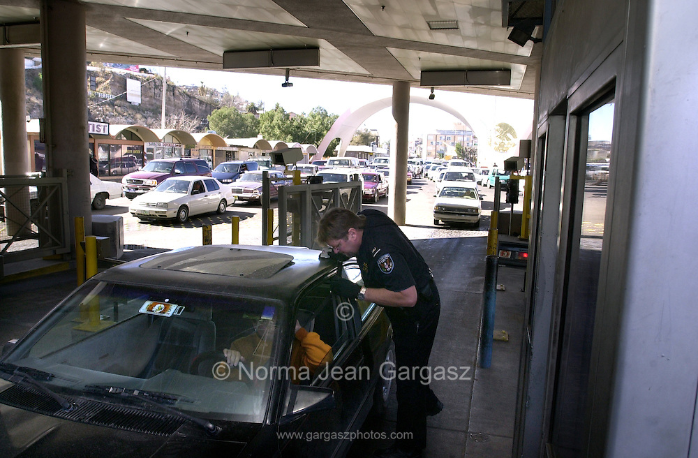 A U. S. Customs inspector processes a vehicle entering the United States from Nogales, Sonora, Mexico at the Dennis DeConcini Port of Entry in Nogales, Arizona.