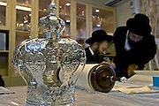 The silver crown that is placed on top of the Sefer Torah (five books of Moses) used to mark the scroll as sacred and holy as it's thought to be the living word of god. In the background a scribe is handwriting the last few words with a quill and ink for an Ashkenazi synagogue in Stamford Hill. A Sefer Torah contains 304,805 letters and can take over a year to produce.