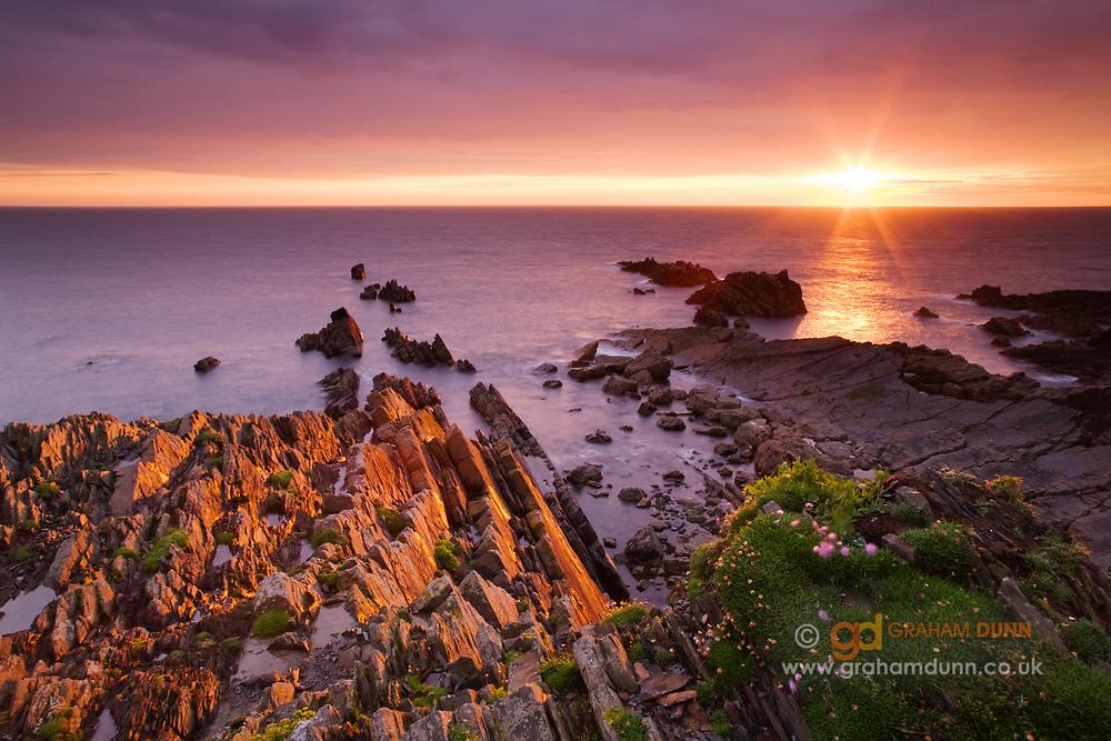 Evening light on Hartland Quay's dramatic rocks. A colourful sunset coastal scene in Devon, England, UK.