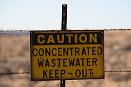 """Water warning sign across from the San Juan Generating Plant just outside of Farmington, New Mexico in the Four Corners region, deemed an 'energy Sacrifice Zone,"""" by the Nixon administration, is one of America's largest coal plants."""