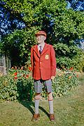 Teenage boy standing in garden wearing brand new secondary school uniform, England, UK, 1960s full length portrait