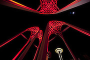 Looking a little like the tendons of heart valves, Pacific Science Center's arches bask in red light, with the Space Needle in the background. (Ellen M. Banner / The Seattle Times)