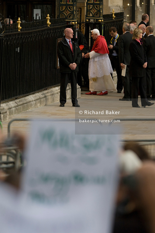 Amid protester's banners, Pope Benedict XVI arrives at Westminster Abbey during his papal tour of Britain 2010, the first visit by a pontiff since 1982. Taxpayers footed the £10m bill for non-religious elements, which largely angered a nation still reeling from the financial crisis. Pope Benedict XVI is the head of the biggest Christian denomination in the world, some one billion Roman Catholics, or one in six people. In Britain there are about five million Catholics but only a quarter of Catholics regularly attend Sunday Mass and some churches have closed owing to spending cuts.