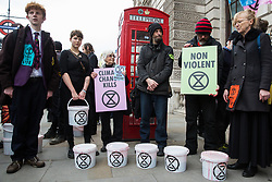 London, UK. 9th March, 2019. Climate activists from Extinction Rebellion prepare to pour artificial blood on the ground outside Downing Street as part of an act of civil disobedience named 'The Blood of Our Children' to call on the Government to take immediate steps to combat the current climate and ecological emergency.