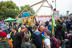 London, UK. 7 October, 2019. Climate activists from Extinction Rebellion build a wooden structure as they block Millbank at one end of Lambeth bridge on the first day of International Rebellion protests to demand a government declaration of a climate and ecological emergency, a commitment to halting biodiversity loss and net zero carbon emissions by 2025 and for the government to create and be led by the decisions of a Citizens' Assembly on climate and ecological justice.