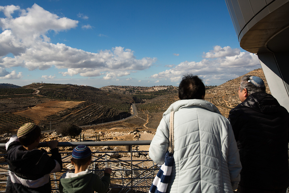 Israelis watch a general view of the West Bank Jewish settlement of Eli from the archaeological park of Ancient Shiloh, which is located at the entrance to the modern Jewish settlement of Shiloh, south of the Palestinian West Bank town of Nablus, on January 1, 2017.