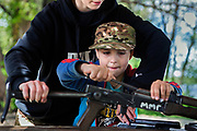 Alongside his instructor, a young boy participating to the ultra-nationalistic Azovets children's camp is learning how to assemble and disassemble a kalashnikov rifle, on the banks of the Dnieper river in Kiev, Ukraine's capital.