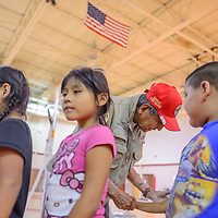 Navajo Code Talker and former Navajo Nation President Peter McDonald greets students at Chichiltah Jones Ranch School Thursday. McDonald and his daughter, Hope McDonald-Lonetree, brought school supplies for the students and made a presentation about local Code Talker Kee Etsicitty.