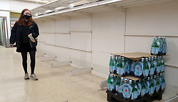 © Licensed to London News Pictures. 31/07/2021. London, UK. A shopper wearing a face covering walks past nearly-empty shelves of bottled drink water in Sainsbury's, north London. Record breaking numbers of people have been forced to self-isolate after being alerted by the NHS Covid-19 app. The pingdemic has seen staff shortages at supermarkets, resulting in less stock making its way to supermarket shelves. Labour leader Sir Keir Starmer has demanded that the government brings forward the end to self-isolation from 16 August to 7 August. Photo credit: Dinendra Haria/LNP