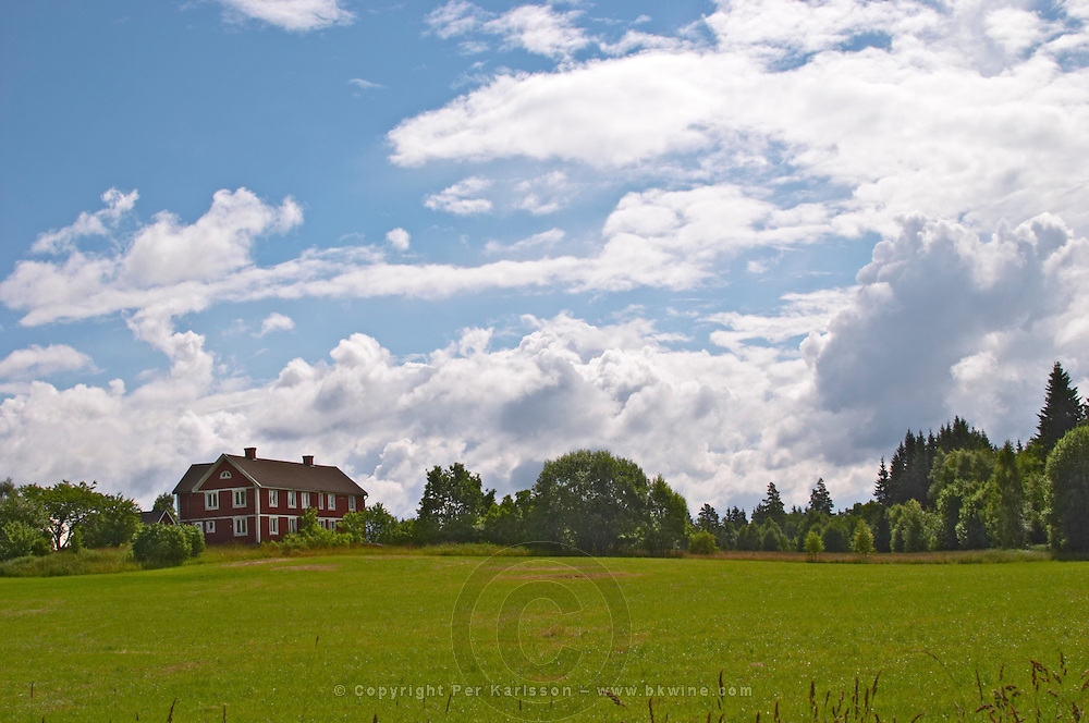 A red farm house barn against a blue sky with clouds and a green field. Smaland region. Sweden, Europe.