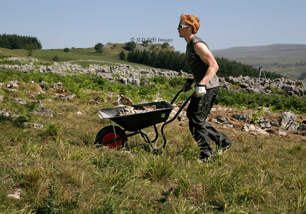 Redheaded Earthwatch volunteer Clay Russell trots a wheelbarrow full of stones up a hill.  He wears sunglasses and gloves but his red hair shouts in the sun.