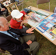 Elderly couple read Red Arrows, Britain's RAF aerobatic team merchandise during publicv local airshow display.