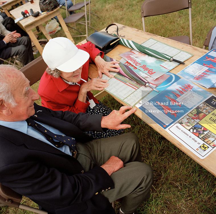 Elderly couple read Red Arrows, Britain's RAF aerobatic team merchandise during publicv local airshow display.