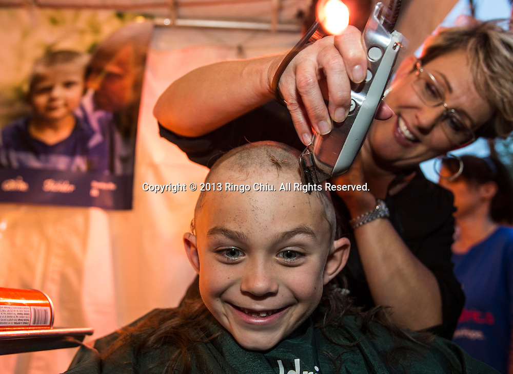 A boy smiles as he has his head-shaving during the annual St. Baldrick's Day head-shaving fundraiser on Thursday, March 14, 2013, in Arcadia, California. More than100 women and men shaved their heads to raises money for child cancer research. The event, ``St. Baldrick's Day,'' is part of a global effort and the world's biggest volunteer-driven fundraising program for childhood cancer. (Photo by Ringo Chiu/PHOTOFORMULA.com).
