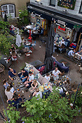 An aerial view of customers enjoying al fresco dining and drinking at a bar at London Bridge in Southwark, on 10th June 2021, in London, England.