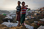 Boys fly a kite on a hill overlooking a refugee camp in Cox's Bazar, Bangladesh.