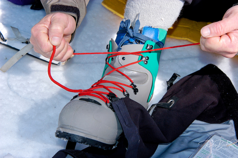 Mountaineer lacing up the plastic outer shell of a double boot, California