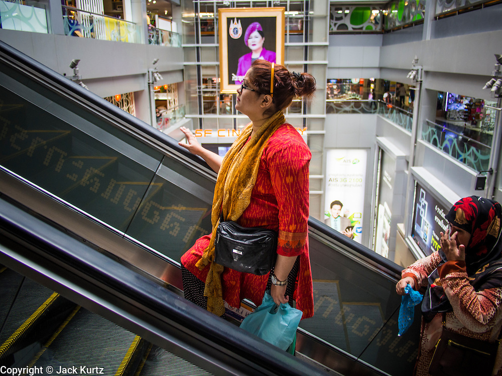 """21 AUGUST 2013 - BANGKOK, THAILAND:    Shoppers ride an escalator in MBK, a large shopping mall in Bangkok. Thailand entered a """"technical"""" recession this month after the economy shrank by 0.3% in the second quarter of the year. The 0.3% contraction in gross domestic product between April and June followed a previous fall of 1.7% during the first quarter of 2013. The contraction is being blamed on a drop in demand for exports, a drop in domestic demand and a loss of consumer confidence. At the same time, the value of the Thai Baht against the US Dollar has dropped significantly, from a high of about 28Baht to $1 in April to 32THB to 1USD in August.    PHOTO BY JACK KURTZ"""