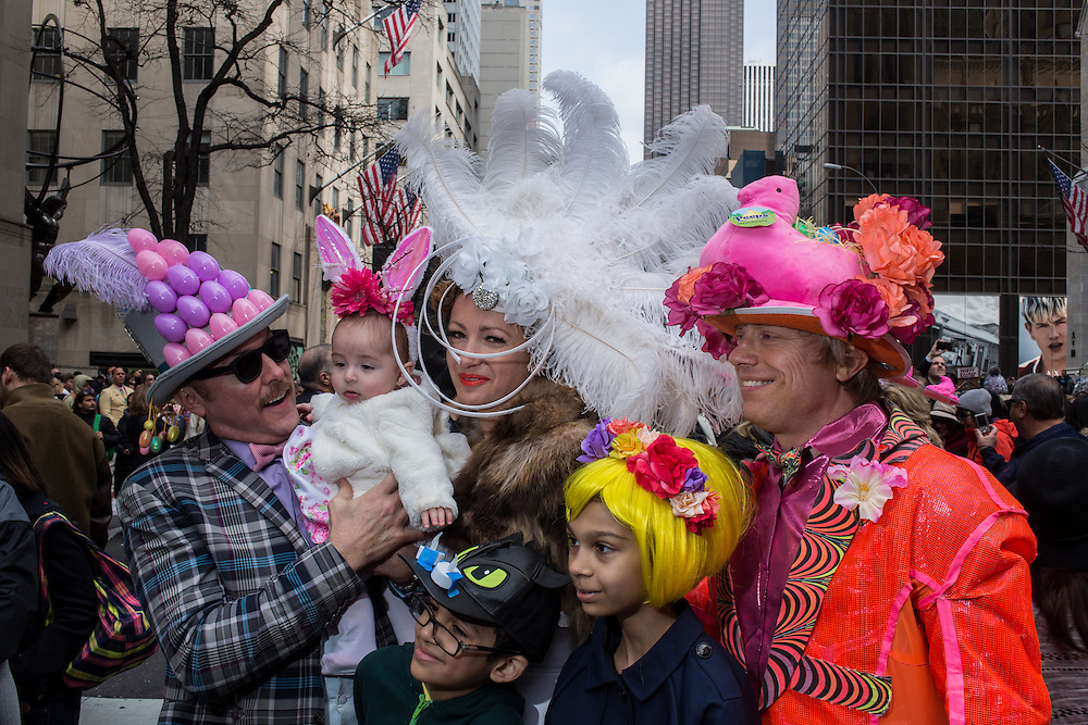 New York, NY, USA-27 March 2016. A group of behatted people pose for photographers in the annual Easter Bonnet Parade and Festival, as the Fifth Avenue crowds pack the street in front of St. Patrick's Catherdral.