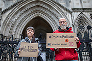 Paid to Pollute claimants Kairin van Sweeden and Jeremy Cox outside the Royal Courts of Justice on 2nd October 2021 in London, United Kingdom. Kairin and Jeremy are two of the three climate activists taking the UK government to court over the billions of pounds of public money it spends supporting the oil and gas industry, as part of the Paid to Pollute campaign. <br /> <br /> Jeremy Cox is a retired former oil worker, current Extinction Rebellion activist, beekeeper, green woodworker and amateur baker.<br /> <br /> Kairin van Sweeden is an SNP Common Weal organiser for the North east of Scotland, the daughter of an oil worker, an Aberdeen quine and Executive Director of the Modern Money Scotland think tank.