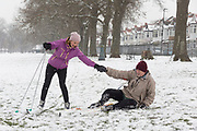 A cross-country skier helps pick up an older companion who has fallen over during their city ski through Ruskin Park in Lambeth, during a snowstorm in the city, on 28th February 2018, in London, England.