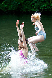 © Licensed to London News Pictures. 25/05/2017. London, UK. Emily Ashbrook and Elizabeth Bailey swim in Hampstead Heath Mixed Bathing Pond in north London as temperatures hit 29C on Thursday 25 May 2017. Photo credit: Tolga Akmen/LNP
