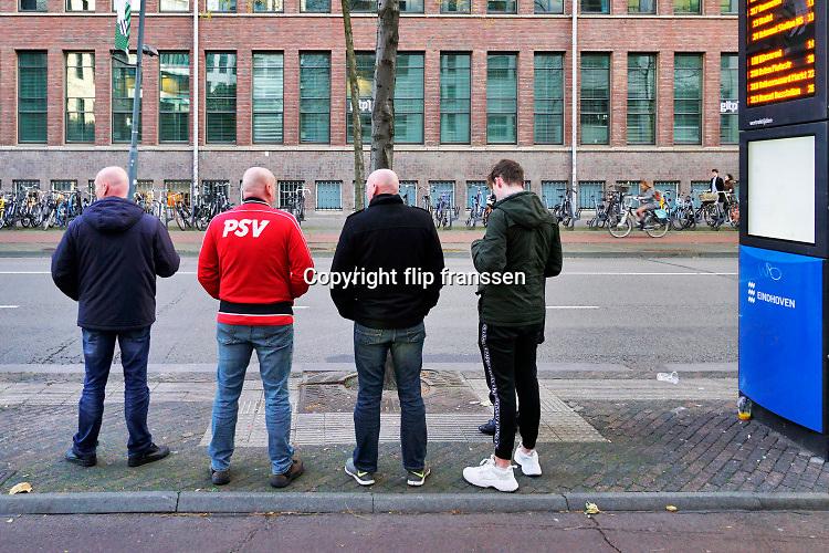 Nederland, Eindhoven, 27-10-2019Supporters, fans, van PSV voetbalclub staan te wachten op de bus bij een bushalte .Foto: Flip Franssen