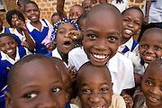 School children happy to finish for the day from a primary school near Kalerwe market, Kampala, Uganda,