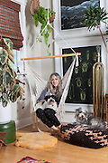 Liz Kamarul sits in her artistically decorated Northeast Portland home with her trusty assistants Cuddi and Bo. Her style, talent for thrift store shopping and decorating have resulted in a substantial instagram following, which she attributes partly to her game changing purchase - the orange couch.<br /> Image by Shauna Intelisano