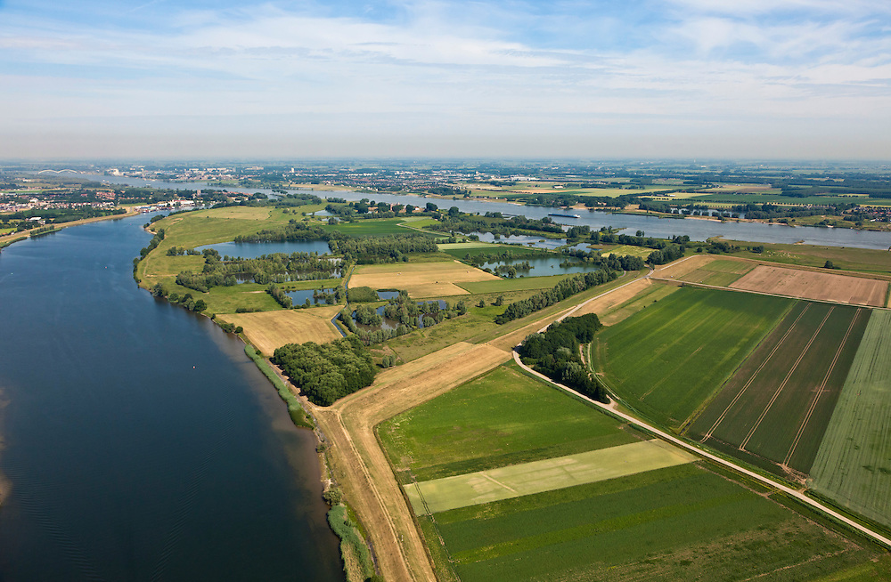 Nederland, Gelderland, Gemeente Brakel, 08-07-2010; Buitenpolder Het Munnikeland. Links de Afgedamde Maas, met links van de monding Woudrichem, rechts Slot Loevestein. Rivier de Waal aan de horizon..In het kader van het programma Ruimte voor de Rivier zijn er plannen om de polder weer als komgebied te gaan gebruiken voor de opvang van water bij hoge waterstanden. De Waalkade wordt verlaagd. .Munnikenland, with nature reserve Munnikhof. Left old river arm Meuse, with left of the river mouth Woudrichem and right Castle Loevestein. Waal River in the distance. Under the program 'space for the river', there are plans to use the polder as retaining basin during high water.  The height of the dike of the river Waal will be reduced..luchtfoto (toeslag), aerial photo (additional fee required).foto/photo Siebe Swart