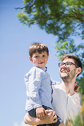 Happy man with his son enjoying picnic in the countryside, Bavaria, Germany