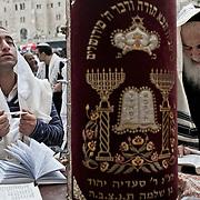 Jérusalem, israël, le jeudi 21 avril 2011 - près de 10 000 fidèles étaient rassemblés au mur des lamentations pour la bénédiction des Cohanim (prêtres juifs) au quatrième jour de Pessah (Pâques juive). Un viel homme récite des prières et un jeune fidèle se reccueille devant un parchemin de la Torah
