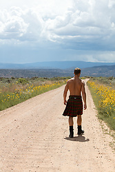 sexy man without a shirt in a kilt outdoors walking on a dirt road
