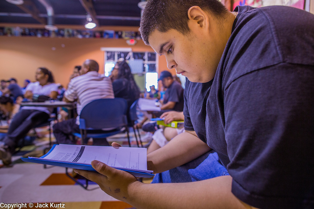 """18 AUGUST 2012 - PHOENIX, AZ:  A young man who hopes to win """"deferred action"""" status goes over paperwork at a deferred action workshop in Phoenix. More than 1000 people attended a series of 90 minute workshops in Phoenix Saturday on the """"deferred action"""" announced by President Obama in June. Under the plan, young people brought to the US without papers, would under certain circumstances, not be subject to deportation. The plan mirrors some aspects the DREAM Act (acronym for Development, Relief, and Education for Alien Minors), that immigration advocates have sought for years. The workshops were sponsored by No DREAM Deferred Coalition.  PHOTO BY JACK KURTZ"""