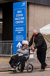 © Licensed to London News Pictures. 18/01/2021. LONDON, UK.  A woman in a wheelchair leaves a vaccination centre at the Olympic Office Centre in Wembley, north London.  This is one of ten new mass Covid vaccination centres opening today and they join the seven already in use across the country.  So far, 3.8 million people across the UK have received a first dose and the government hopes that number to rise to 15 million by 15 February.  Photo credit: Stephen Chung/LNP