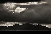 A thin strip of bright sunlight illuminates the Irish Sea in otherwise ominous heavy weather at Caernarfon Bay, on the Northern coast of the Llyn Peninsula. The distinctive three peaks of Yr Eifl, Tre'r Ceiri, Garn Ganol and Garn For can be seen under the dark clouds.