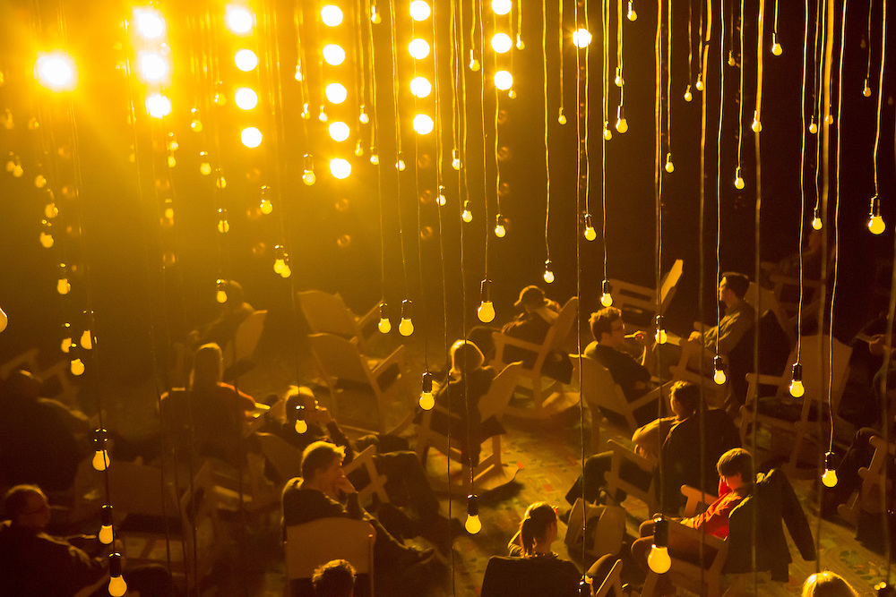 The audience seated in rocking chairs, bathed in yellow light, with pendant light bulbs overhead.
