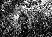 Camopi, Guyane, 2015.<br /> <br /> Culturellement, les amérindiens ne conçoivent pas l'individu en dehors d'une collectivité qui inclue les humains, les non humains, les choses visibles et les choses invisibles. L'Homme fait partie d'un tout et le droit de l'individu n'a pas réellement de sens si ce n'est celui d'assumer ses fonctions d'être vivant. <br /> Le droit français privilégie lui, les droits de l'individu. <br /> <br /> Toujours liés à leur environnement naturel dans un système relativement autarcique fait de chasse, de pêche et culture de manioc, les amérindiens de Guyane sont maintenant placés dans une situation de dépendance jusque-là inconnue. La situation des habitants de Camopi apparaît comme la plus négative.<br /> <br /> La première école de Camopi a été ouverte en 1955 mais sa fréquentation ne se généralise qu'après la création de la commune en 1969. L'argent arrive ici au début des années 70 peu après la citoyenneté française. À l'époque chaque famille cultive encore un abattis, la chasse et la pêche restent un apprentissage quotidien pour les jeunes enfants. Dans un premier temps, l'école républicaine qui n'a pas pour fonction de perpétuer la diversité culturelle et l'éloignement imposé par l'internat des enfants dans un institut catholique de Saint-Georges mettent un frein à la transmission de ces savoirs. Par la suite, l'arrivée des allocations familiales consacre la fin d'une certaine organisation sociale où la polygamie est largement pratiquée et favorise la structuration du foyer autour du couple pour permettre la distribution des allocations. Plus récemment, le RMI et maintenant le RSA institutionnalisent l'attribution d'aides à titre individuel qui servent à payer les cartouches ou l'indispensable essence des pirogues et créent des envies et des frustrations.<br /> <br /> Aujourd'hui, des prêts à la consommation sont finalement proposés aux habitants de Camopi. Toute cette succession de bouleversements récents conduit à une réelle perte d'