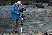 USA, Oregon, Heceta Head Lighthouse State Park, photographer recording time lapse of clouds around Heceta Head Lighthouse, (MR)