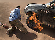 A driver fixing a tire by injecting flammable gaz and setting it on fire. The explosion resets the tire in the wheel.