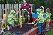 Children dressed in green stripes, working and playing in the nursery school garden, with their carer. University Hospital of South Manchester (UHSM) has a creche on site looking after 80 of their staff's children. A strong sense of community has been integral to the development of the hospital, and due respect from their staff has helped them achieve their goals. Manchester, United Kingdom.