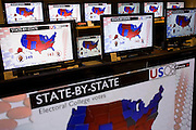 Live BBC News broadcasts a breakdown of College votes results the morning after Barack Obama's historic victory in the 2008 Presidential election. The TV screens are in he audio and electronics floor of the John Lewis department store in Oxford Street, London, England. A newly-elected Barack Obama is seen speaking to his party faithful at the rally in Chicago, and his face is large on the many home cinema screens seen across the world's media after this historic political election which saw the election of America's first black Commander in chief. A shopper stops to watch the lunchtime news programme as Obama speaks with passion about the changes he promises to bring to America while the rest of the world looks on hoping for new political directions.