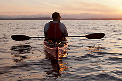 United States, Washington, Seattle.  A man paddles a sea kayak in Elliott Bay at sunset, looking west to the Olympic Mountains. MR