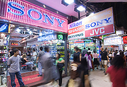 People walk past consumer electronics shop at night in Kowloon district of Hong kong