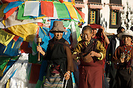 Tibetan pilgrims pass by a pole decorated with hundreds of prayer flags in Barkor Square in Lhasa, Tibet.