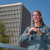 Biologist Courtney McCammon surveys the horizon for raptors circling above Wilshire Boulevard in Los Angeles, CA. A hawk nest sits on a window ledge behind her (visible).