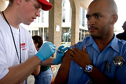 10 Sept 2005. New Orleans, Louisiana.  Hurricane Katrina aftermath.<br /> NOPD officer Matt Robinson is injected with a hepatitis shot by paramedic Brian White of the Mobile Medical Response team at the bottom of Canal Street.<br /> Photo; ©Charlie Varley/varleypix.com