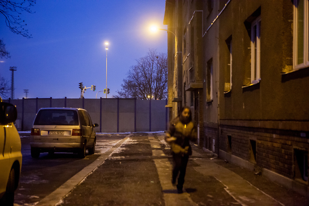 Street scene in the city of Ostrava - a girl running in front of a wall protecting the inhabitants of the neighbourhood of sound coming from a close by city highway.